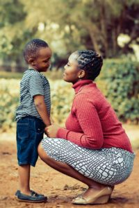 Woman bent down talking to small boy
